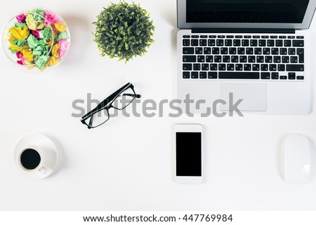 Top view of white office desktop with blank mobile phone, coffee cup, glasses, laptop, computer mouse and decorative items. Mock up