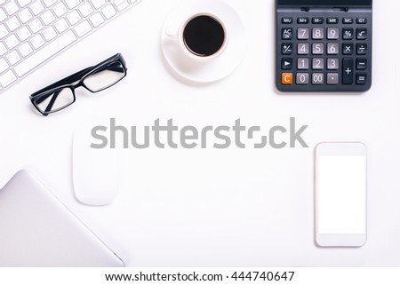 Top view of white office desktop with blank smart phone, calculator, coffee cup, glasses, closed laptop, computer mouse and keyboard. Mock up