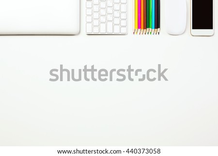 Top view of white office desktop with closed laptop, computer keyboard, colorful pencils, mouse and smart phone. Mock up - stock photo