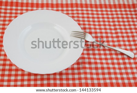 Top view of white plate and fork on tablecloth