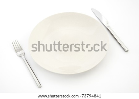 top view of white plate, fork and knife, restaurant tableware