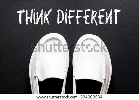 Top View of White Shoes on the black floor with the word - Think Different - stock photo