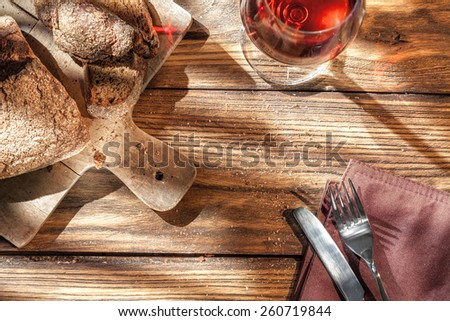 Top view of wine and bread on wooden table with fork and knife - stock photo