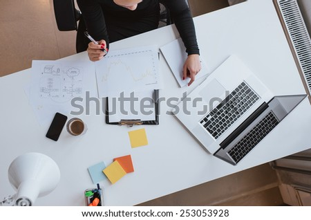 Top view of woman executive working at her desk with chart and laptop. Reviewing financial data and plotting progress thus far. - stock photo