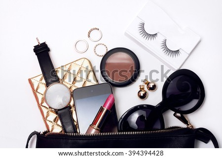 Top view of woman fashion accessories . Trendy sunglasses, black bag , watch , lipstick ,blusher , notebook , smart phone - stock photo
