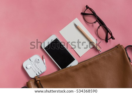 Top view of woman hipster traveler stuff with phone,notepad,glasses,earphone and brown handbag on pink background
