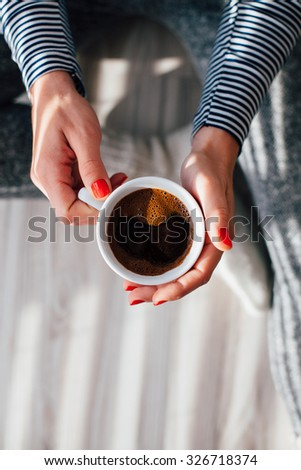 Top view of woman holding a hot cup of coffee - stock photo