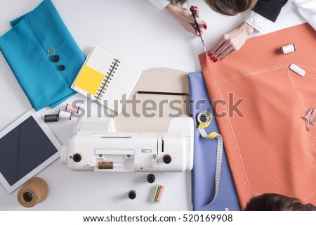 Top view of woman holding scissors and red material with pattern drawn on it about to start cutting and sewing