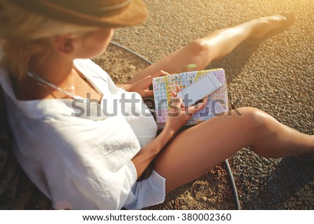 Top view of woman traveler with location map holding mobile phone with blank copy space screen for your text message or content, female tourist chatting on cell telephone while sitting on the ground  - stock photo