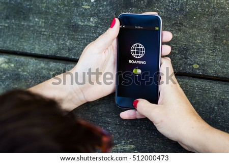 top view of woman using smartphone to check roaming. All screen graphics are made up.