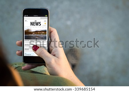 Top view of woman walking in the street using her mobile phone reading news in the screen with copyspace. All screen graphics are made up. - stock photo