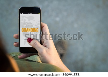Top view of woman walking in the street using her mobile phone with branding on screen. All screen graphics are made up. - stock photo