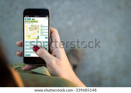 Top view of woman walking in the street using her mobile phone with car sharing on screen with copyspace. All screen graphics are made up. - stock photo