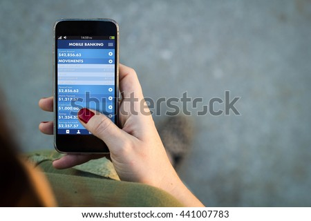Top view of woman walking in the street using her mobile phone with mobile banking app. All screen graphics are made up.