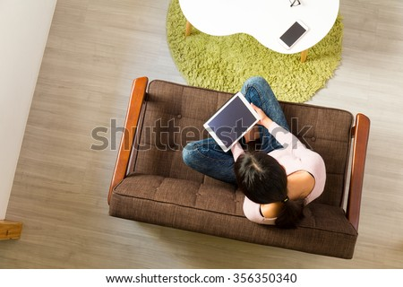 Top view of woman watching on tablet pc and sitting on sofa - stock photo