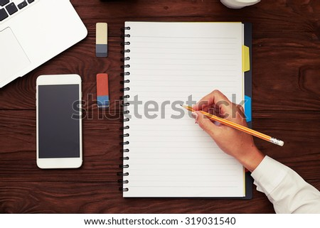 top view of womans hand holding pencil and ready to writing on empty white notepad over wooden table - stock photo