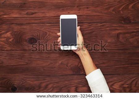 top view of womans hand with white smartphone over brown wooden background - stock photo