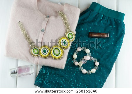 Top view of women's clothing set on white wooden background - stock photo