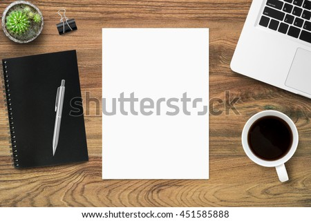 Top view of wood office desk table with supplies and blank a4 paper in the middle.  Top view, flay layout. - stock photo