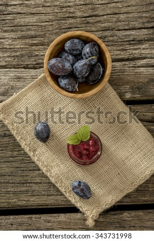 Top view of wooden bowl full of fresh ripe plums, a jar of home made plum marmalade decorated with mint leaves and two juicy plums lying on a linen textile over textured rustic wooden boards. - stock photo