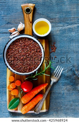 Top view of wooden cutting board with raw red rice and fresh vegetables ingredients for tasty cooking over dark rustic background. Healthy eating or vegetarian concept. - stock photo