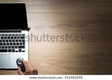 Top view of wooden desktop with male hand listening to computer using stethoscope. Mock up - stock photo