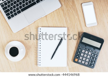 Top view of wooden office desktop with blank white cellphone, spiral notepad with pen, coffee cup, calculator and notebook keyboard. Mock up