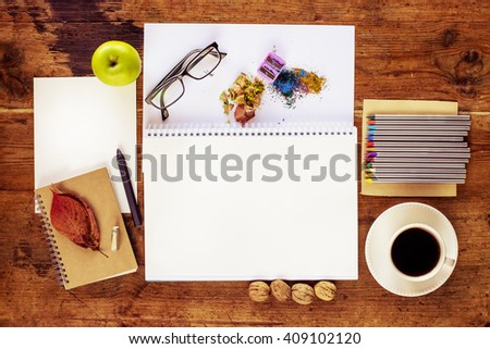 Top view of wooden table. Mock-up of art work with colored pencils, apple, glasses, autumn leaves and blank sketch book page.  - stock photo