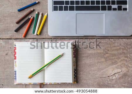 Top view of work desk with computer and blank notebook on wooden background