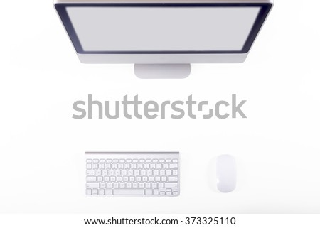 Top View of Working Place of Designer with large Computer Monitor Keyboard and Mouse on White Desk grey Screen - stock photo