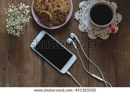 Top view of working space office, smart phone with blank screen,laptop, earplug,a cup of coffee and blank paper note on wood table, flat lay. - stock photo