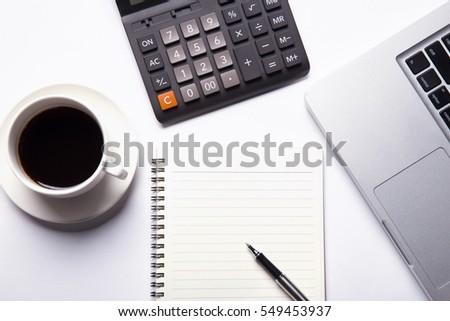 Top view of working space with blank notebook page, laptop, calculator, hot coffee and pen. Top view. Business planning concept on white.