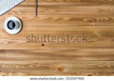 Top view of workplace with cup keyboard pencil on wooden table - stock photo