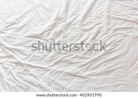 Top view of wrinkles on a messy bedsheet in a hotel / motel / inn  room, an unmade bed after a long night sleep. A pattern can be used for several creative design or for abstract texture background. - stock photo