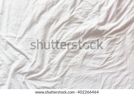 Top view of wrinkles on an untidy white bed sheet in a bedroom after a long night sleep and waking up in the morning. A pattern can be used for making a wavy flag by distort / displacement map method. - stock photo