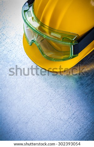 Top view of yellow hard hat with transparent protective glasses on scratched metallic background construction concept. - stock photo