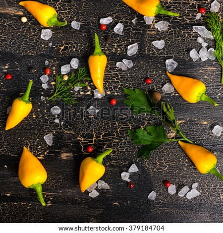top view of yellow hot chili peppers, sea salt, greenery on cracks black background, close up   - stock photo