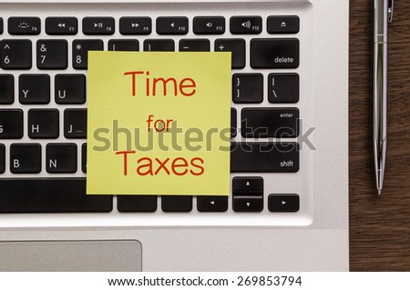 """Top view of yellow notepad with words """" Time for Taxes """" putting on laptop keyboard and stainless steel pen on wood table - stock photo"""
