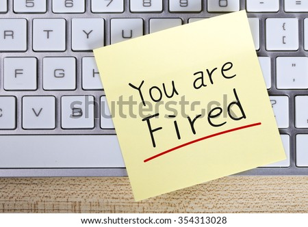 Top view of You Are Fired sticky note pasted on the keyboard. - stock photo