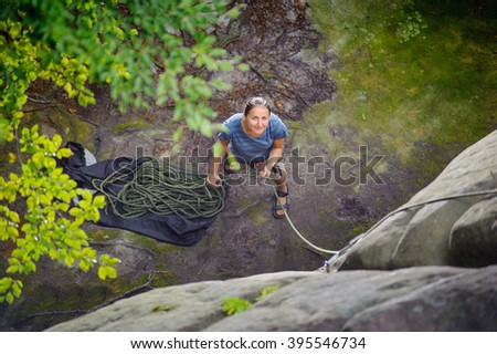 Top view of young athletic woman belaying and watching another climber with rope. Summer time. Climbing equipment.