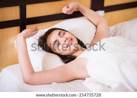 Top view of young beautiful, woman is waking up fully rested. - stock photo