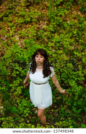 top view of young brunette woman in white dress standing on green grass background nature