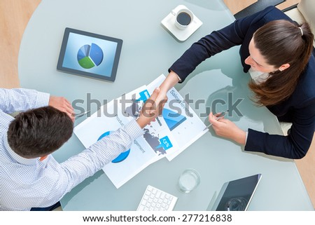 Top view of young business partners shaking hands on deal at desk in office.Documents and digital tablet on table showing statistics and graphics. - stock photo