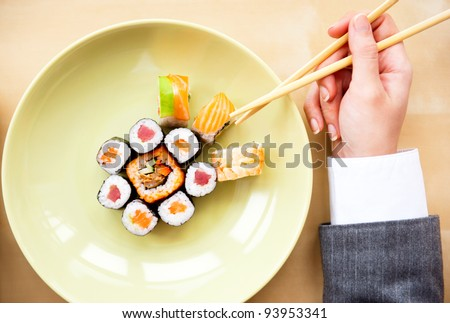 Top view of young business woman wearing suit holding sushi sticks in her arms. Sushi rolls set on plate. Business lunch offer concept - stock photo