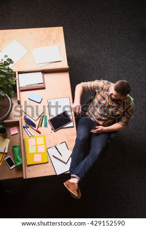 Top view of young businessman sitting with his legs on table while working in office. Handsome man in casual having rest and relax. - stock photo
