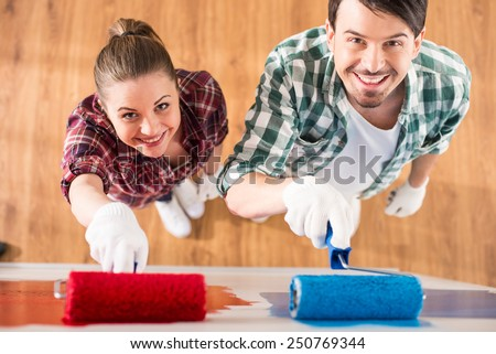 Top view of young couple are doing repair at home and painting a wall with roller. - stock photo