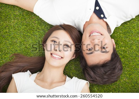Top view of young couple in love lying together on the grass - stock photo