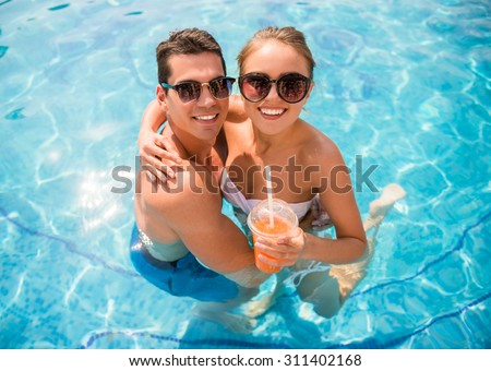 Top view of young couple relaxing in resort swimming pool and drinking cocktails. - stock photo