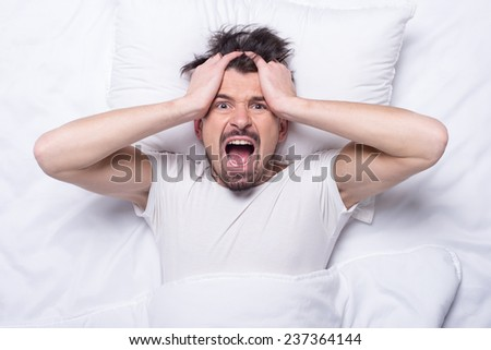 Top view of young emotional man is lying in the bed.