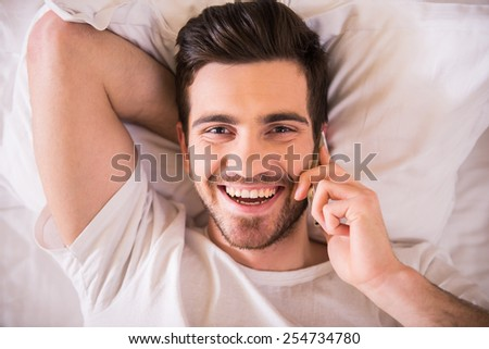 Top view of young handsome man is lying on bed, holding phone and looking at the camera. - stock photo